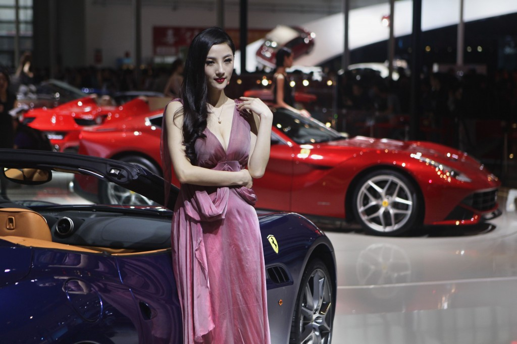 Una modella posa vicino a una Ferrari California al Salone dell'automobile di Pechino